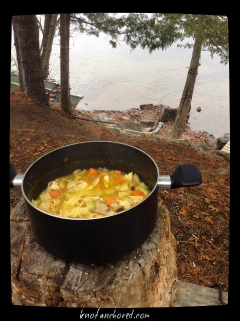 pot of chicken noodle soup, log, lake, outdoors