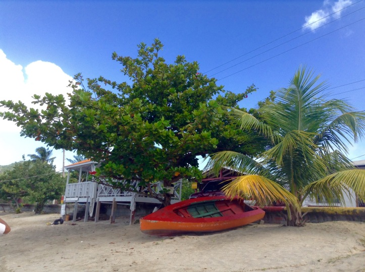 White wood house on the beach, red kayak, Tyrrel Carricou