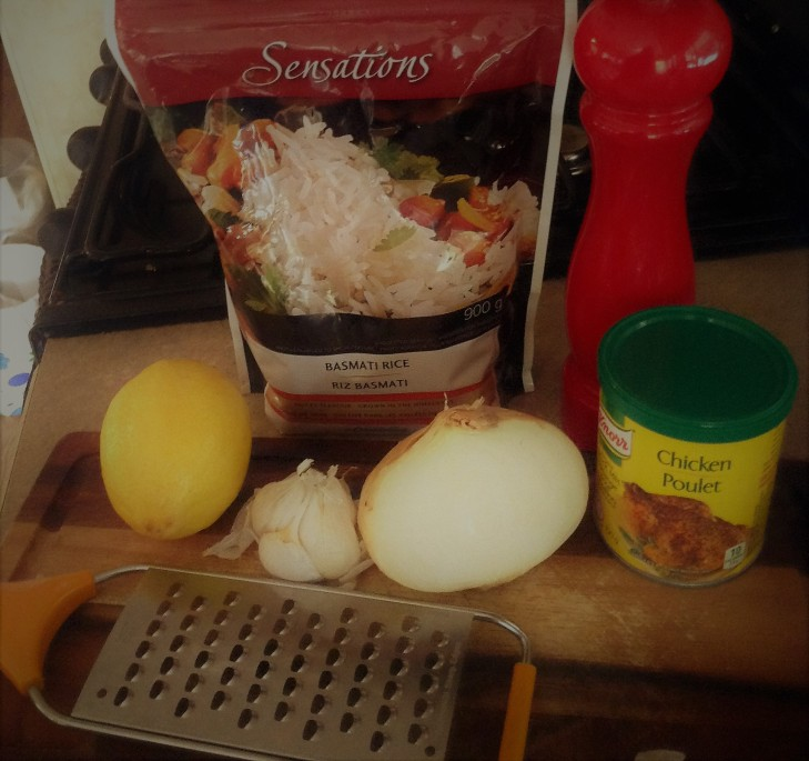 knorr chicken boullion, sensations basmati rice bag, lemon, garlic, grater, onion, wood cutting board
